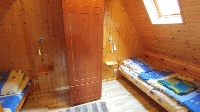 łóżka w sypialni wraz z szafą
