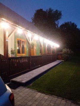 dom w ogrodzie nocą