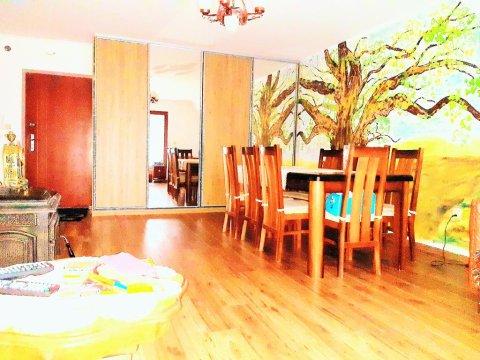 Bardzo słoneczny salon z dużym, rodzinnym stołem oraz z przestrzenną szafą wnękową.