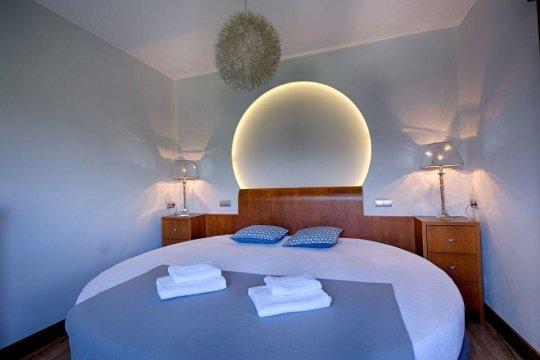 Sypialnia z dużym łóżkiem okrągłym i kominkiem.