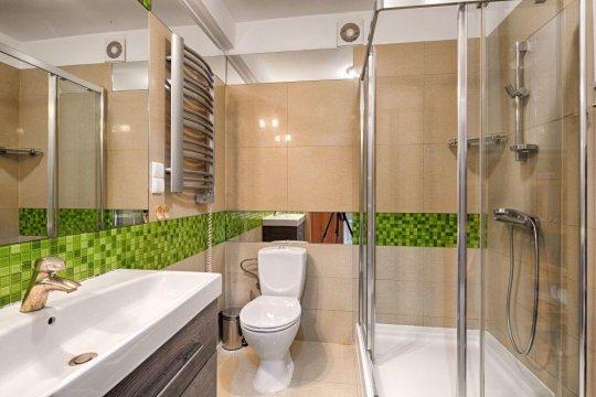 Łazienka z kabiną prysznicową, toaletą, umywalką i dużym lustrem.