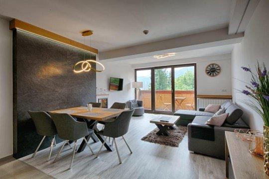 Salon z wygodną sofą, telewizorem, stołem, balkonem.