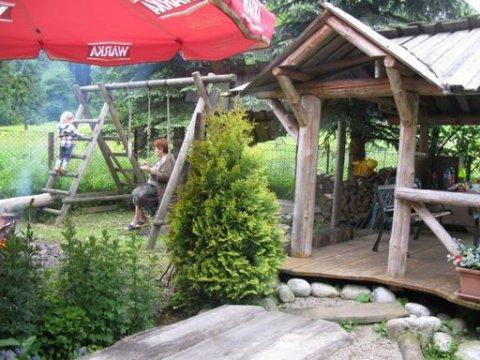 Altana i plac zabaw z miejscem na ognisko w ogrodzie